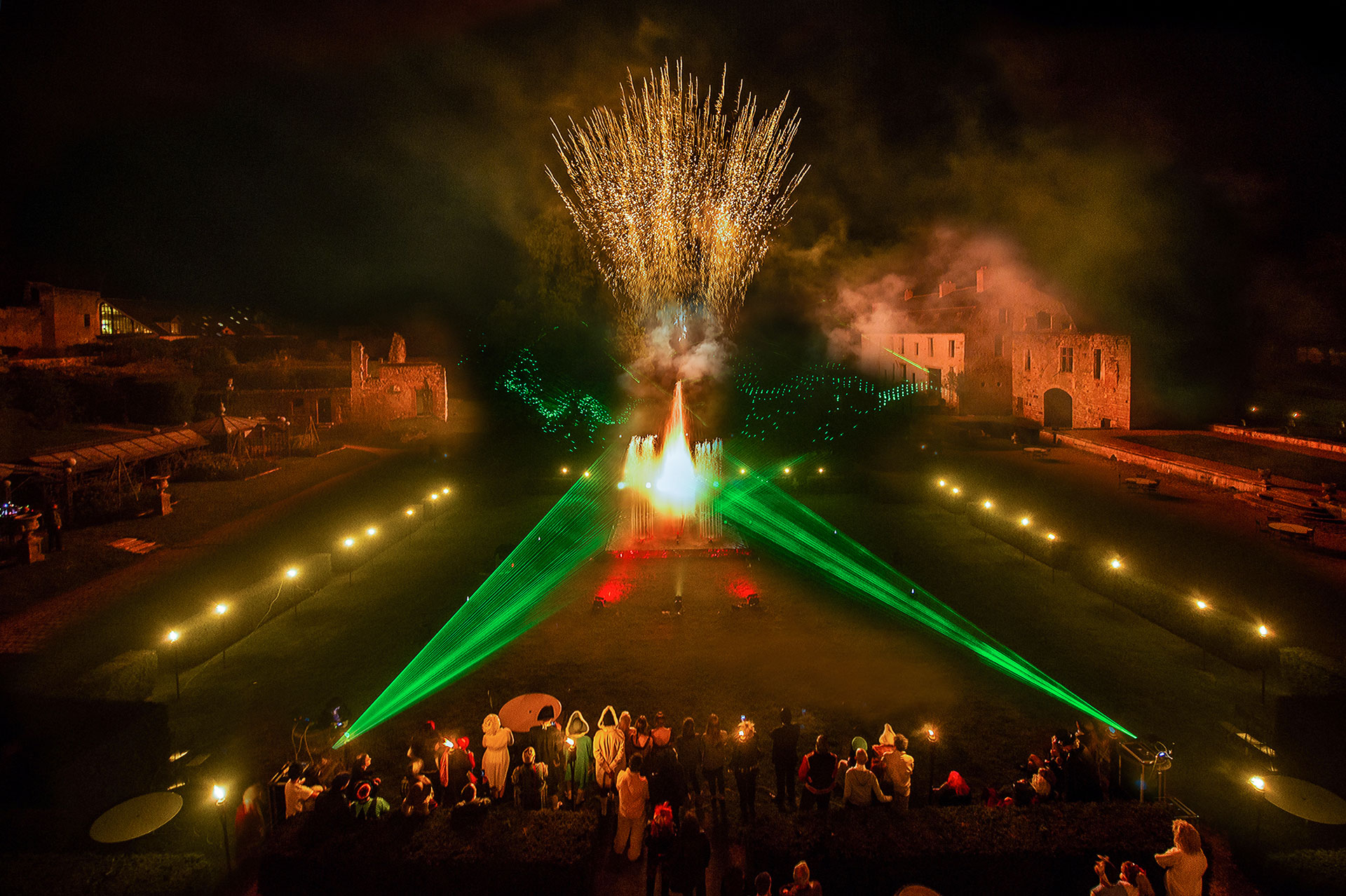 les convives de la réception sortent dans le parc du château pour le spectacle d'eau, de laser et de feu